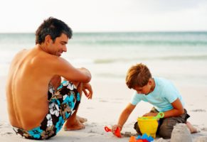 Happy father and son on a beach vacation, boy making sand castle
